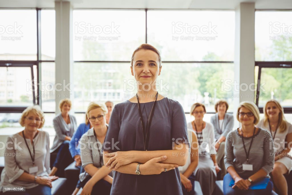 Senior presenter with audience in background Portrait of senior female presenter standing in a seminar hall with audience in background Adult Stock Photo