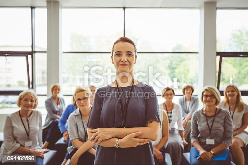 854811490 istock photo Senior presenter with audience in background 1094462596