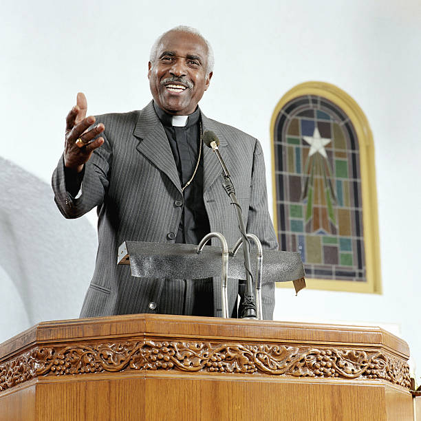 Senior priest giving sermon, smiling, low angle view  pulpit stock pictures, royalty-free photos & images