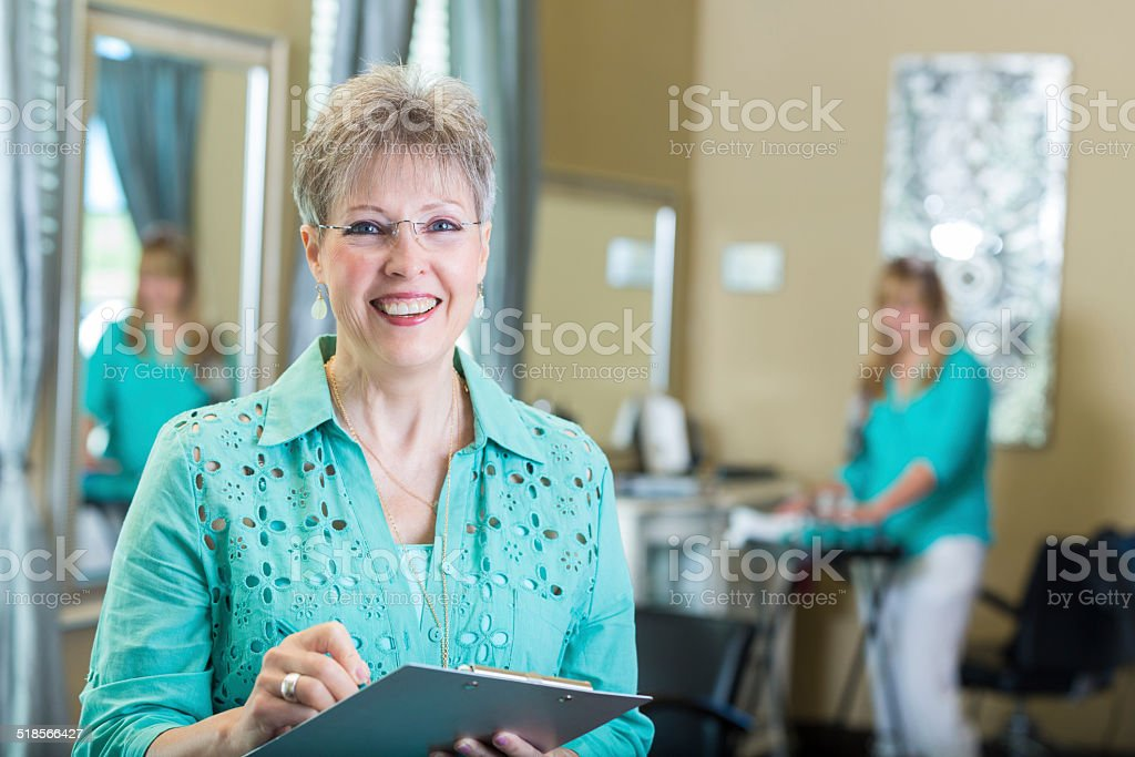 senior professional hairstylist in salon using digital tablet royalty free stock photo - Professional Hairstylist