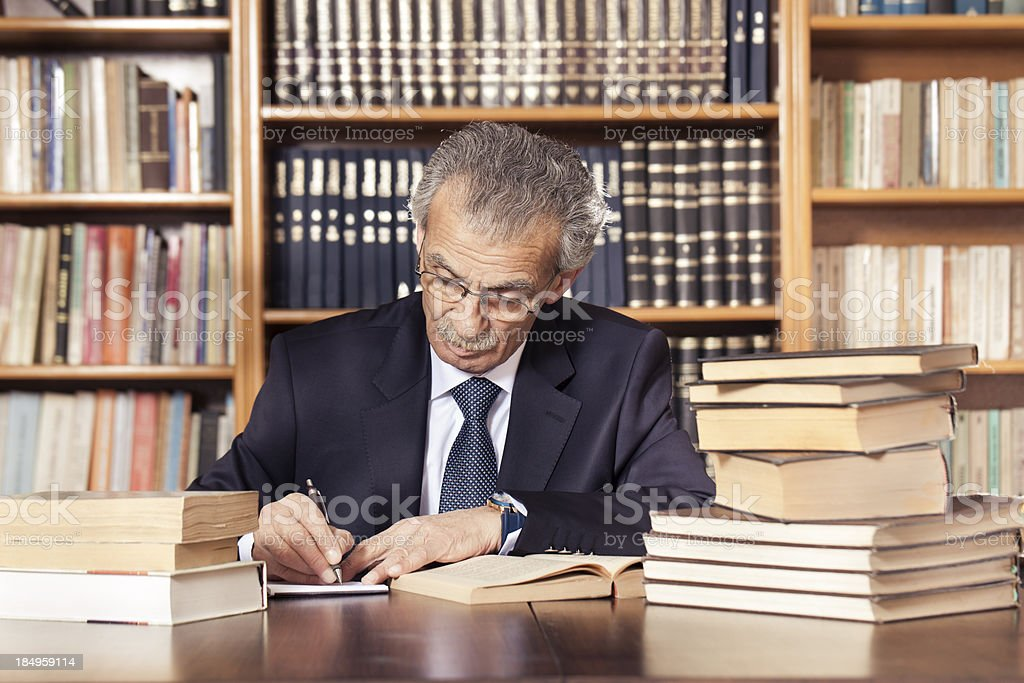 Senior professor working in the library royalty-free stock photo