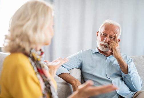 Senior male mental health professional listening to senior woman's problems / Senior couple having an argument.