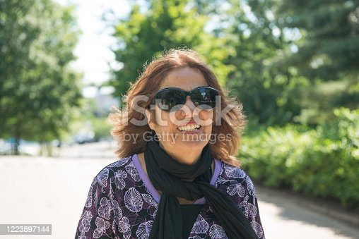 This photograph is of a smiling Puerto Rican woman in her 70s walking outdoors in a Nashville, Tennessee park while visiting on vacation.
