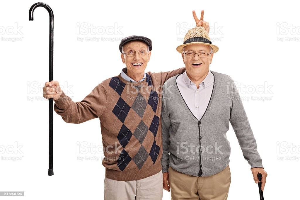 Senior pulling a bunny fingers prank on his friend stock photo