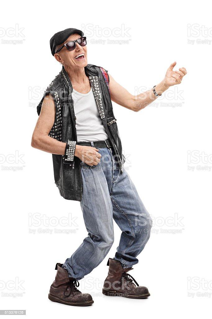 Senior punk rocker playing air guitar stock photo