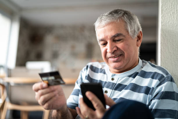 Senior purchasing some itens on the internet Browsing for bargains phone charging stock pictures, royalty-free photos & images