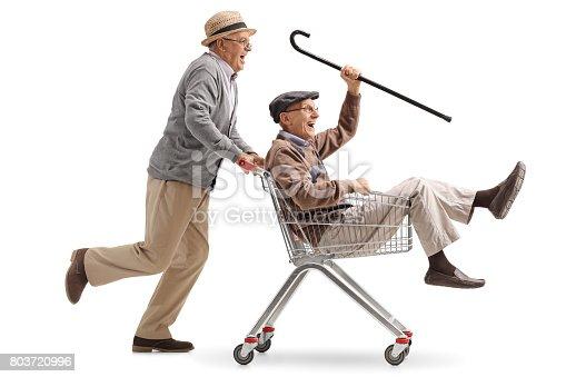 istock Senior pushing another senior in a shopping cart 803720996