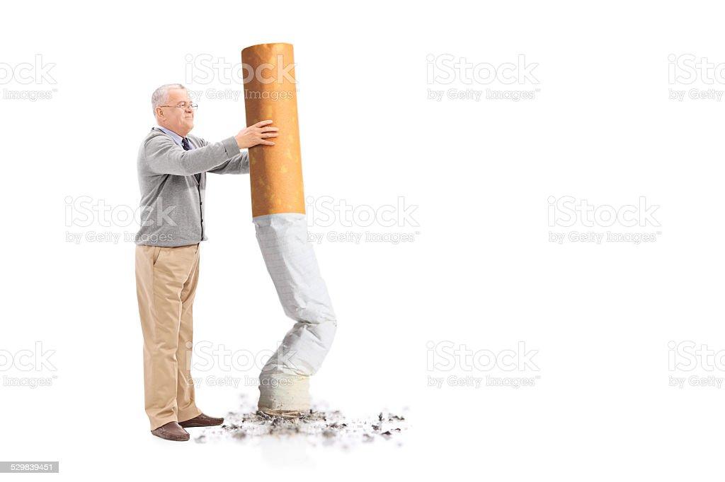 Sênior apagar um cigarro gigante - foto de acervo