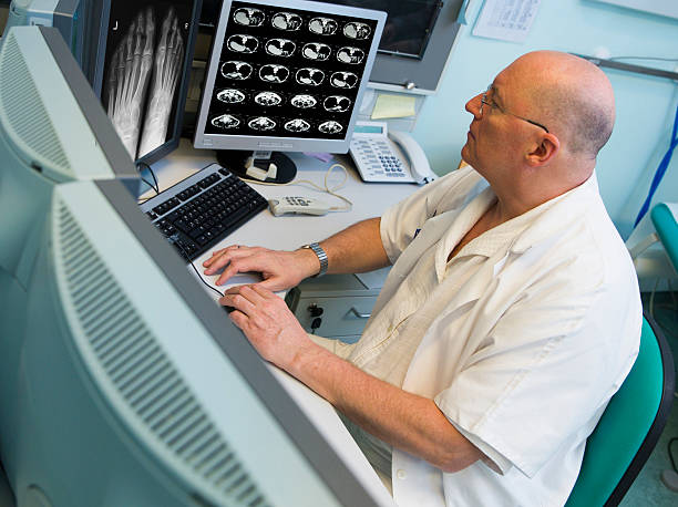 Senior radiologist of Oncology institute is examing MRI scans Senior radiologist of Oncology institute is examing MRI and CAT scans of human abdomen on his monitors human pancreas stock pictures, royalty-free photos & images