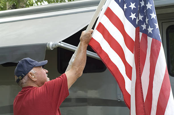 Senior Raising Flag At RV Campground stock photo