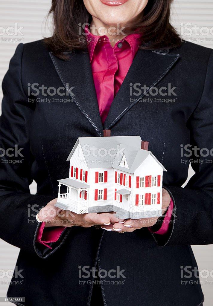 senior real estate woman holding miniature house royalty-free stock photo