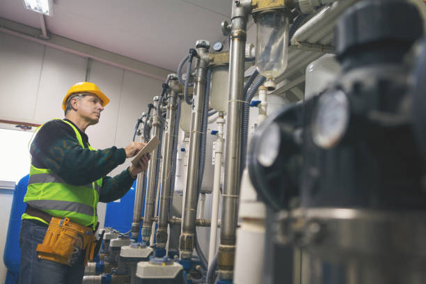 Senior repairman in boiler room checking pipes stock photo