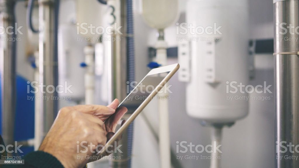 Senior repairman in boiler room checking pipes stock photo