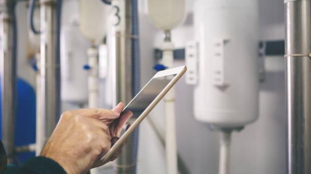 técnico sênior na sala da caldeira, verificando tubos - equipamento industrial - fotografias e filmes do acervo