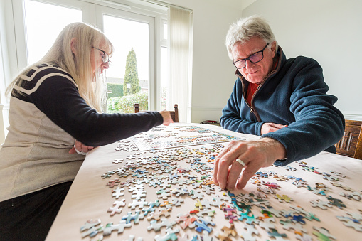 Color image depicting a senior caucasian couple, in their 60s and 70s, doing a jigsaw puzzle together at home during the coronavirus (Covid-19) pandemic. The couple are both wearing spectacles and are concentrating on completing the puzzle together. Room for copy space.