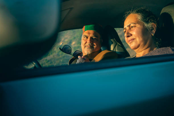 Senior retired couple sits in a car and talks. stock photo