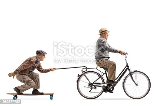 istock Senior riding a bike with another senior riding a longboard and pulling himself with a cane 980877782