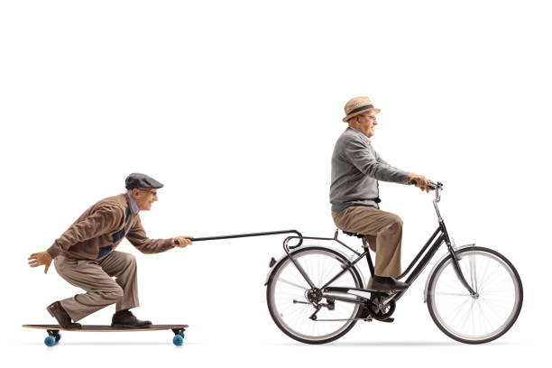 Senior riding a bike with another senior riding a longboard and pulling himself with a cane Senior riding a bike with another senior riding a longboard and pulling himself with a cane isolated on white background young at heart stock pictures, royalty-free photos & images