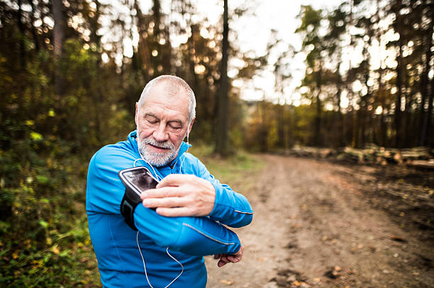 Senior runner in nature with smart phone and earphones. stock photo