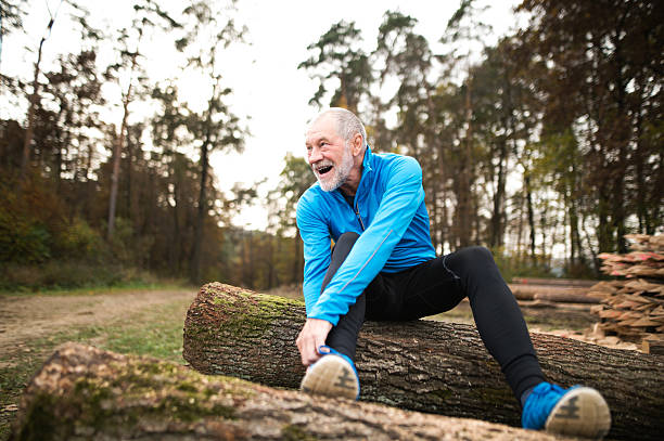senior runner sitting on wooden logs, man resting, stretching. - old man feet stock photos and pictures