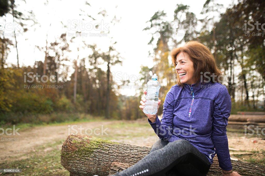 Senior runner sitting on wooden logs, resting, drinking water. stock photo