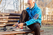 Senior runner tying sneakers in public park