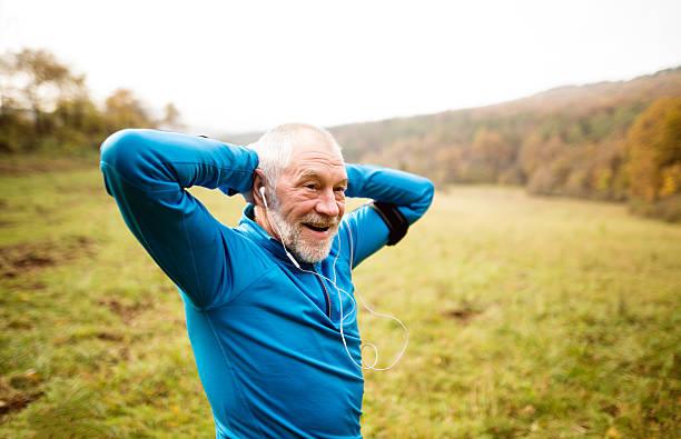 senior runner with armband doing stretching. autumn nature. - motivationsmusik stock-fotos und bilder