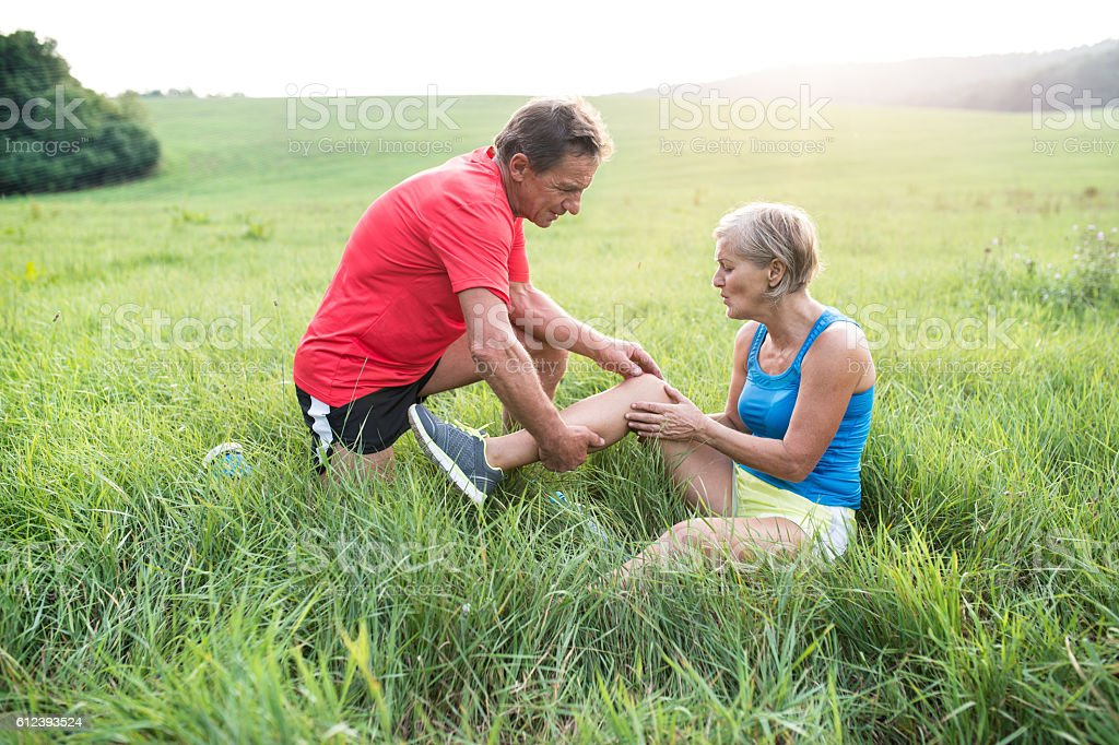 Senior runners in green field. Woman with injured knee. stock photo