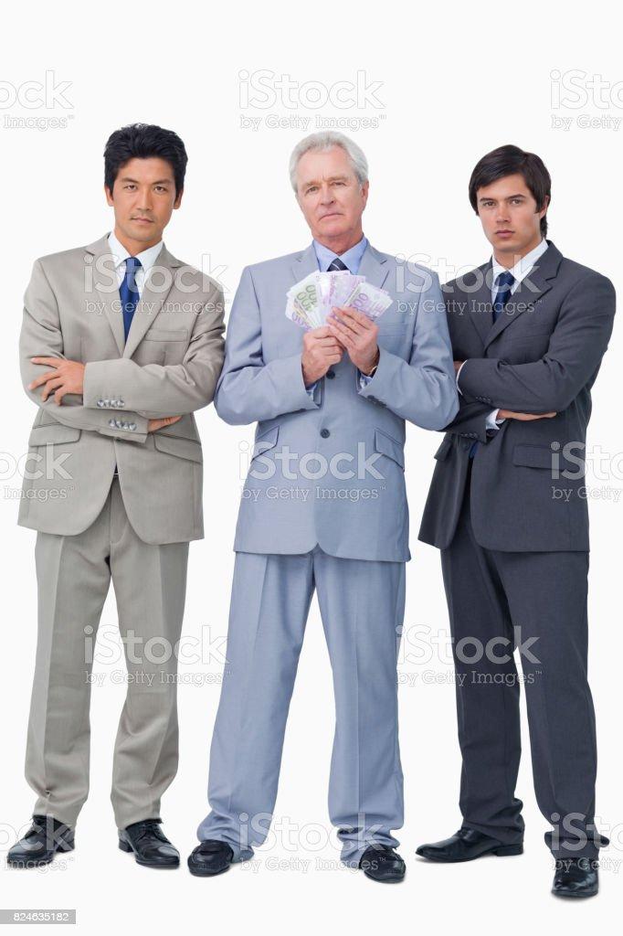 Senior salesman with money and his employees stock photo