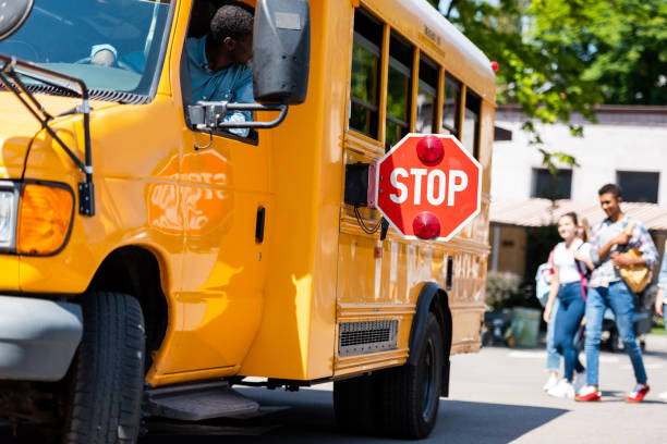 senior school bus driver looking at teens walking behind bus - school bus stock photos and pictures