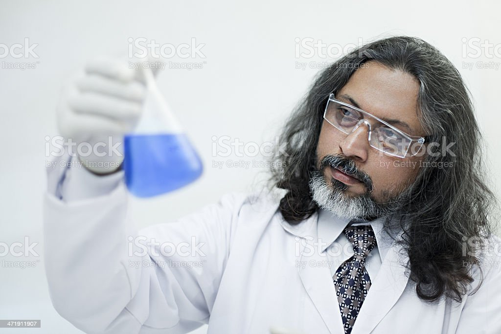 Senior scientist holding flask filled with chemical and analyzing the...