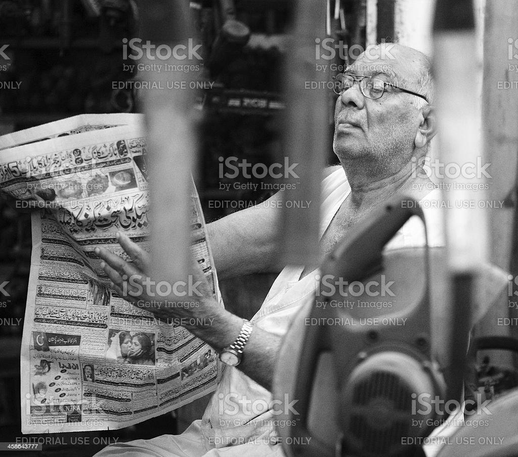 Senior Scrap dealer reading newspaper in Karachi Shershah Kabari stock photo