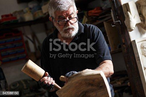 istock Senior sculptor working on his sculpture 542088150