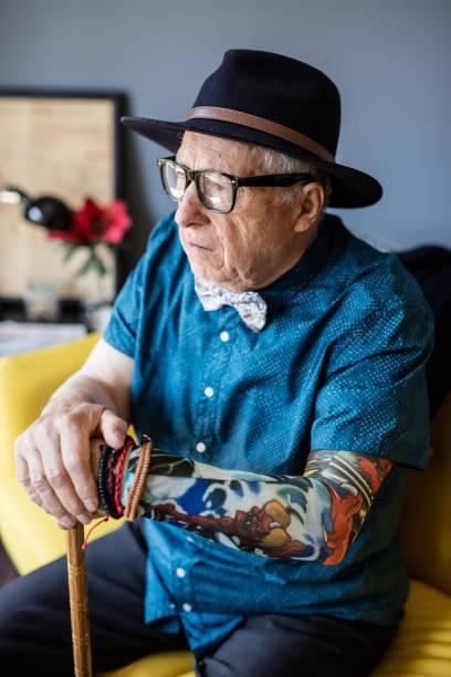 senior ernster mann mit tattoo hält sein kann und auf der suche troug fenster - alte tattoos stock-fotos und bilder