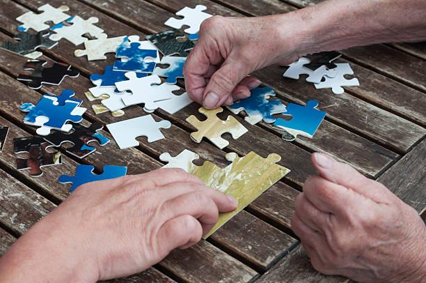 Senior sets puzzle together stock photo
