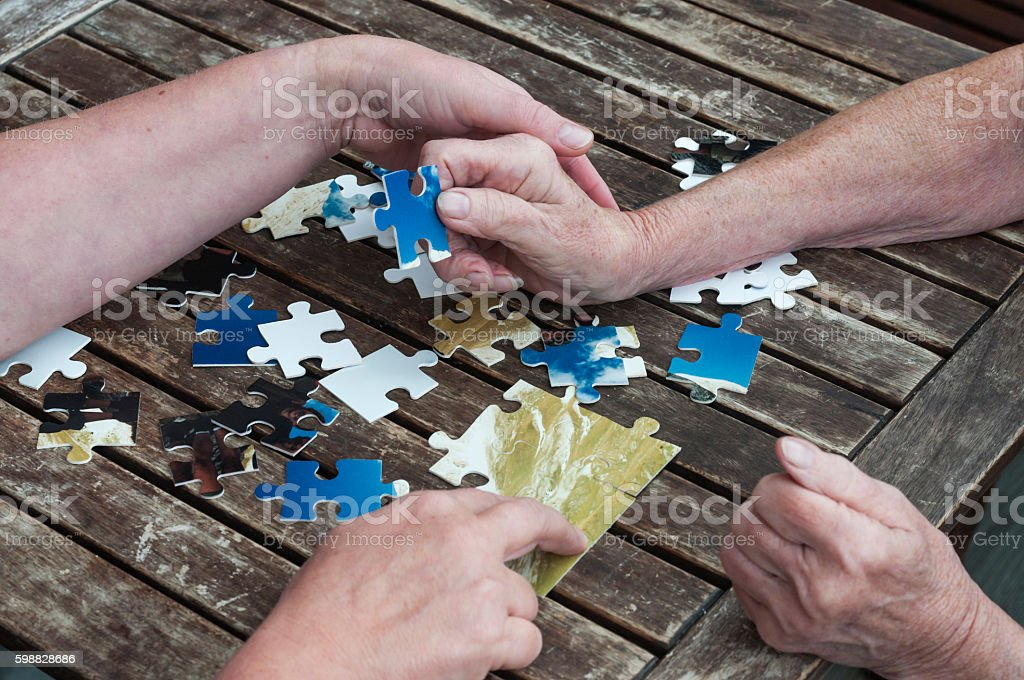 Senior sets puzzle together stock photo