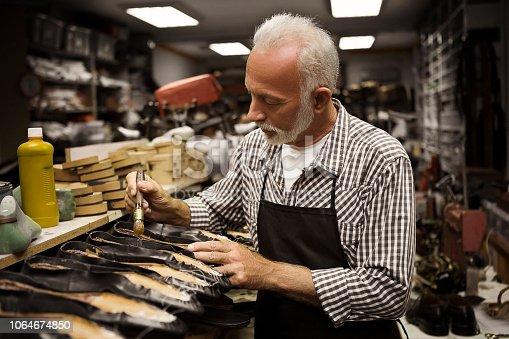 Shoe maker holding brush ,gluing shoe
