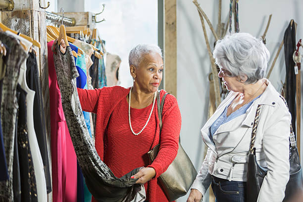 senior shoppers in a clothing store looking at rack - 70 jahre kleidung stock-fotos und bilder