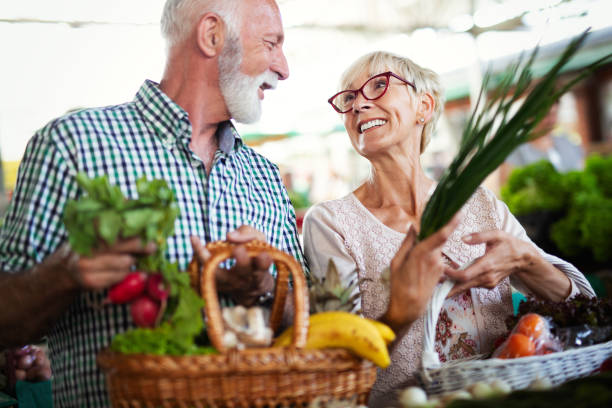 Senior shopping couple with basket on the market. Healthy diet. stock photo