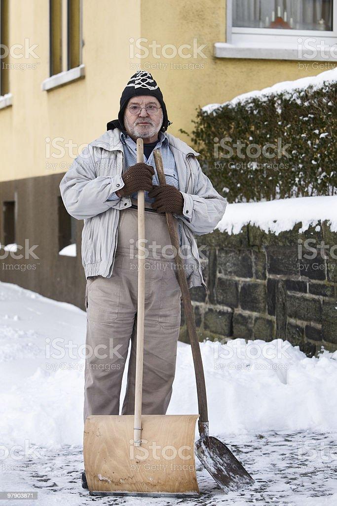 Senior Shovelling Snow stock photo