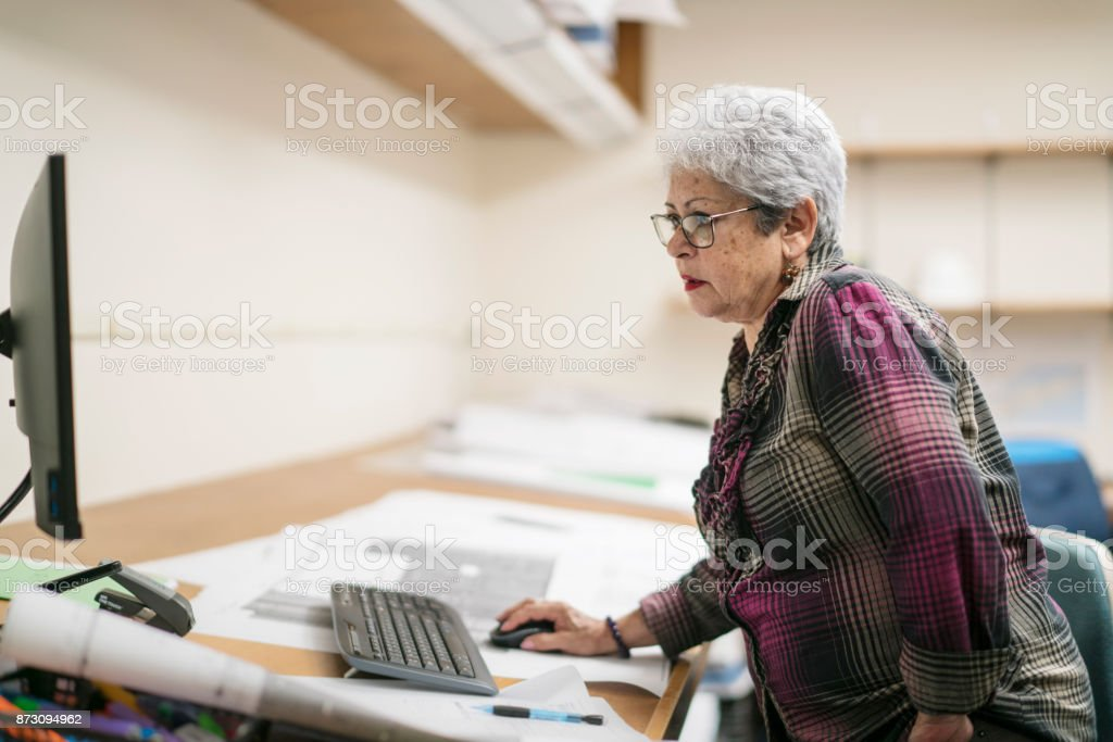 Senior silver-haired woman, engeneer, measuring the space on the...