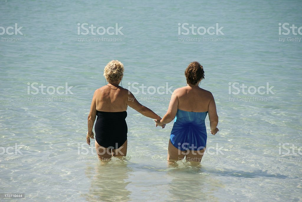 Senior Sisters Hold Hands Wading into Tropical Sea royalty-free stock photo