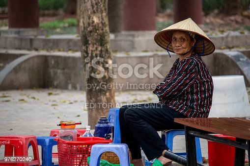 Hanoi, Vietnam - March 16, 2018: Local vietnamese woman sitting in her bar with small plastic chairs located in a park