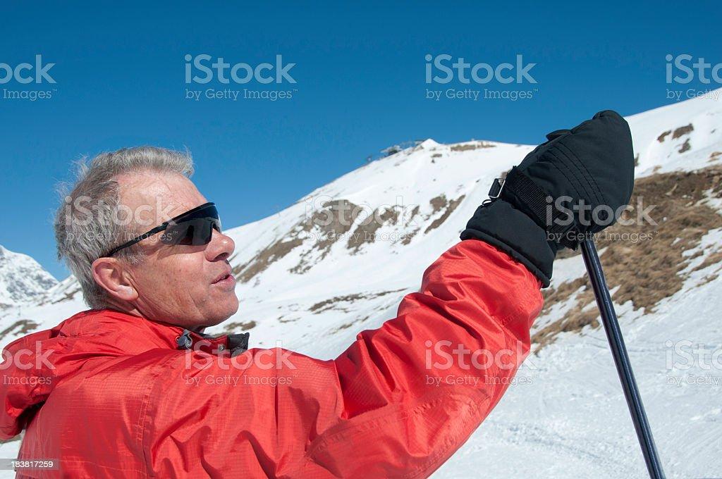 Senior skier pointing with ski pole at mountains stock photo