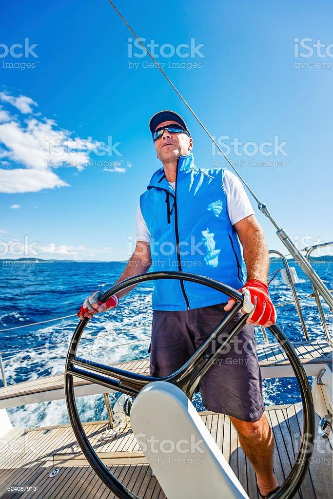 Senior skipper sailing with sailboat stock photo
