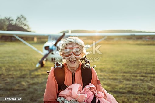 Close up of a senior skydiver next to a plane