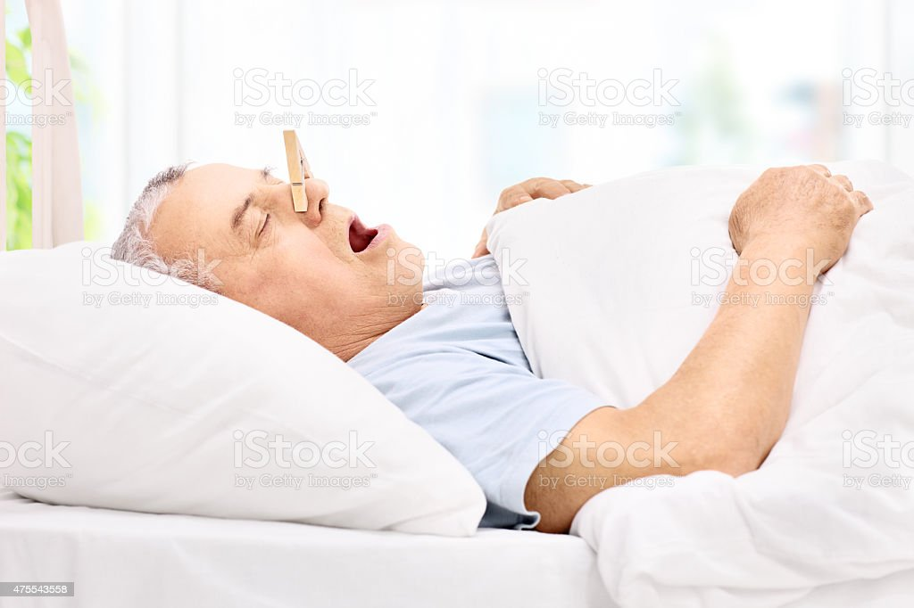 Senior sleeping with a clothespin on his nose stock photo