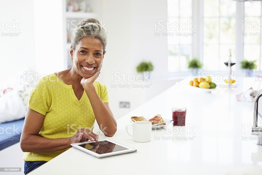 Senior smiling African American woman using tablet at home stock photo