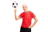 Cheerful senior in a red sports jersey spinning a football on his finger isolated on white background