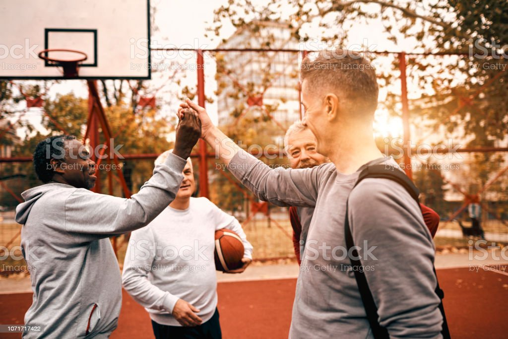 Group of Senior Men Basketball Outdoors. Giving high-five to each...